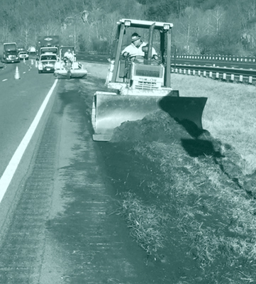 Dozer Plowing Dirt on Shoulder of Highway