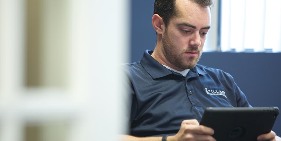 Pillar Employee Analyzing Data on Tablet
